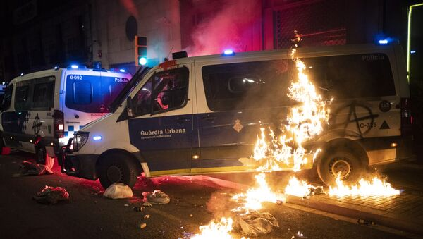 A police van is set on fire as protestors throw molotov cocktails at police during clashes following a protest condemning the arrest of rap singer Pablo Hasél in Barcelona, Spain, Saturday, Feb. 27, 2021. - Sputnik International