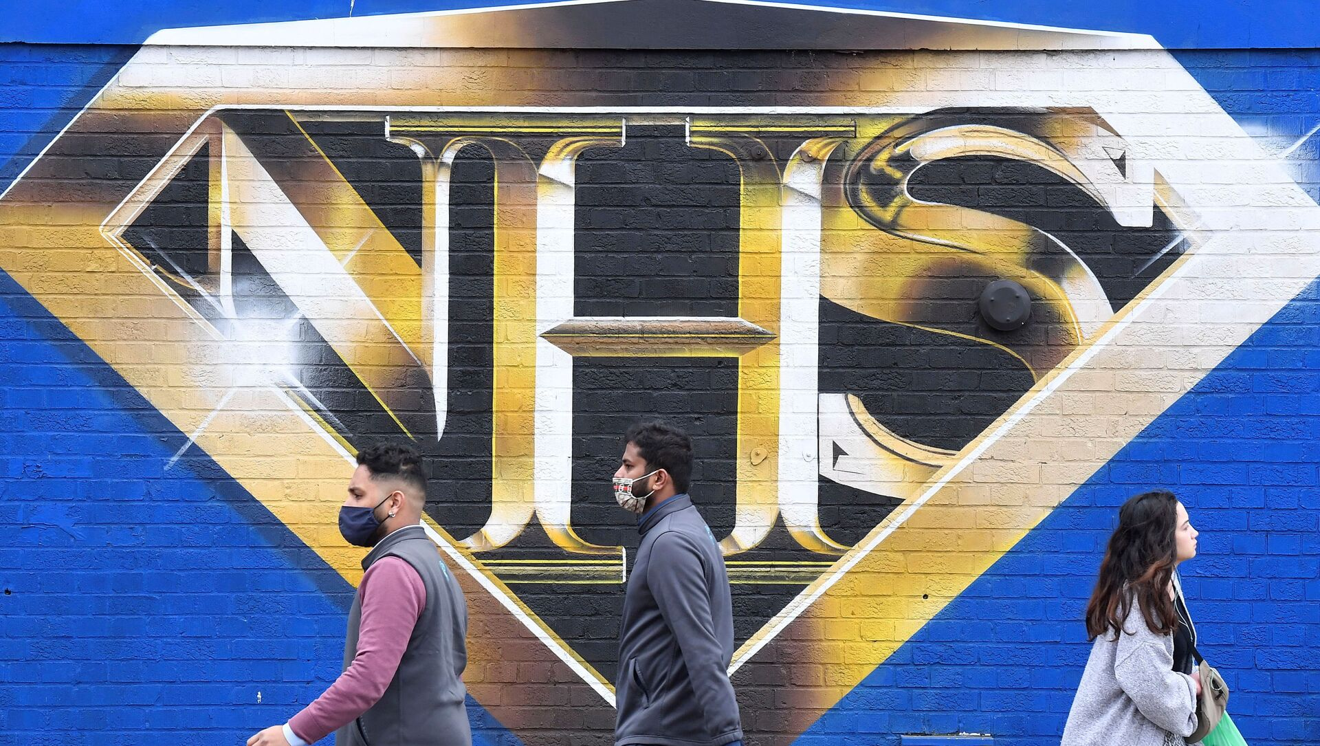 People walk past a mural praising the NHS (National Health Service) amidst the continuation of the coronavirus disease (COVID-19) pandemic, London, Britain, March 5, 2021.  - Sputnik International, 1920, 23.07.2021