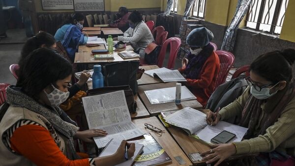 Teachers attend online classes with their mobile phones as sanitization work is in progress  prior to its reopening for higher classes after the spread of the Covid-19 coronavirus, at a private school in Kolkata on February 3, 2021. - Sputnik International