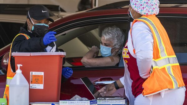 FILE - In this Jan. 26, 2021, file photo, a woman is vaccinated inside her vehicle at a mass COVID-19 vaccination site outside The Forum in Inglewood, Calif. Several states are loosening their coronavirus restrictions on restaurants and other businesses because of improved infection and hospitalization numbers but are moving cautiously, in part because of the more contagious variant taking hold in the U.S. - Sputnik International