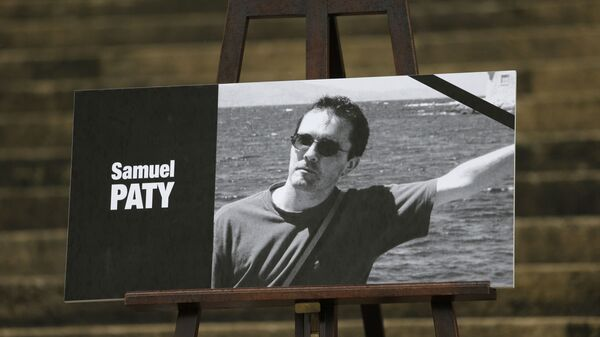 The portrait of slain teacher Samuel Paty with a black ribbon is displayed Tuesday, Oct.20, 2020 on the steps of the National Assembly in Paris. - Sputnik International