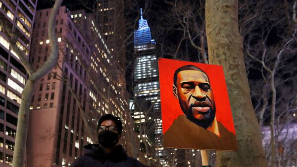 A demonstrator holds up an image of George Floyd during a rally on the first day of the trial of former Minneapolis police officer Derek Chauvin, on murder charges in the death of Floyd, in New York City, New York, U.S., March 8, 2021.  - Sputnik International