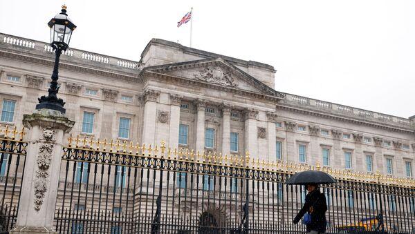 A woman holding an umbrella walks past Buckingham Palace as the snow falls. - Sputnik International
