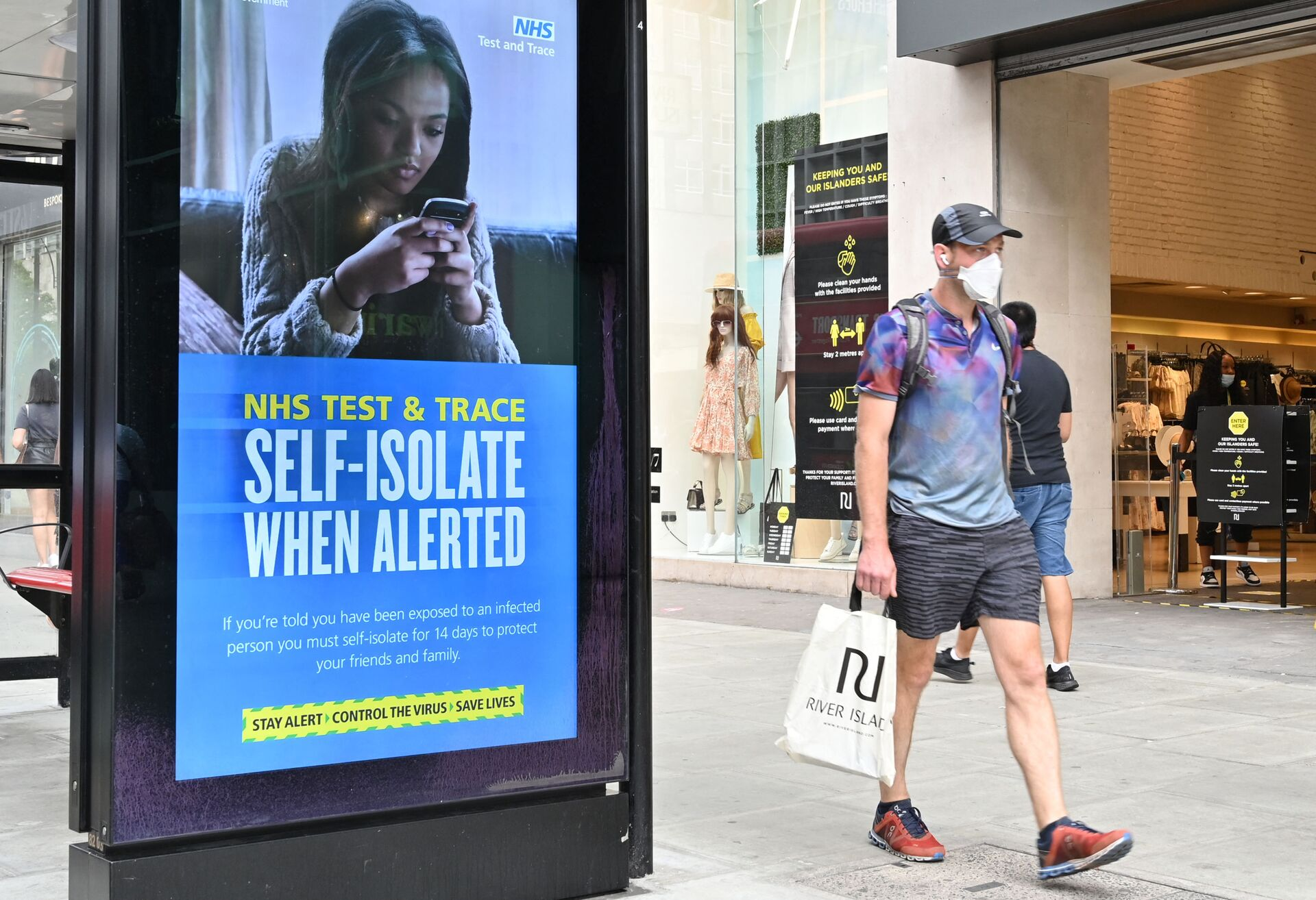 A shopper walks past an advertisment for the UK government's NHS Test and Trace system in Regent Street in London on June 15, 2020 as some non-essential retailers reopen from their coronavirus shutdown - Sputnik International, 1920, 07.09.2021
