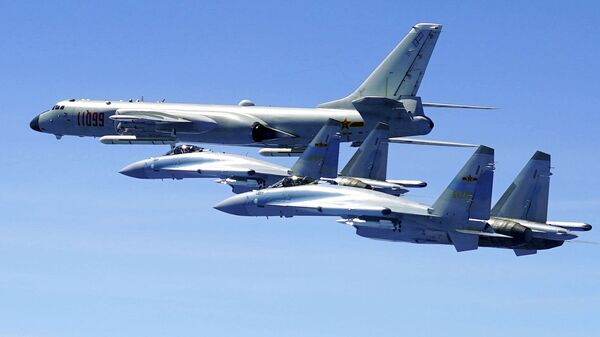 In this photo released by Xinhua News Agency and taken Friday, May 11, 2018, two Su-35 fighter jets and a H-6K bomber from the People's Liberation Army air force fly in formation during patrol that included the Luzon Straits also known as Bashi Straits near Taiwan - Sputnik International