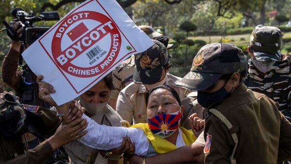 A Tibetan holds a placard as she is detained by police officers during a protest held to mark the 62nd anniversary of the Tibetan uprising against Chinese rule, outside the Chinese Embassy in New Delhi, India March 10, 2021 - Sputnik International
