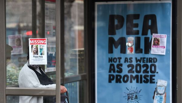 A person sits at a bus stop next to signs that show pictures of Sarah Everard, who disappeared last week, as police continue to search parts of Clapham, in London, Britain, March 10, 2021 - Sputnik International
