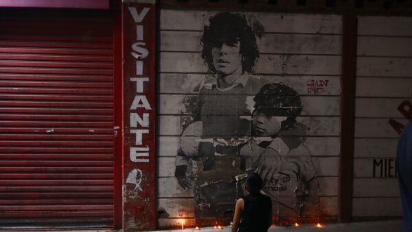 A boy kneels in front of a mural of Diego Maradona decorated with canddles outside the stadium of Argentinos Juniors soccer club, where he started as a professional footballer, in Buenos Aires, Argentina, Wednesday, Nov. 25, 2020. The Argentine soccer great who was among the best players ever and who led his country to the 1986 World Cup title died from a heart attack on Wednesday at his home in Buenos Aires. He was 60.  - Sputnik International