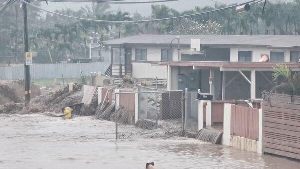 Social media video grab shows floodwaters streaming down a street in Hauula, Hawaii - Sputnik International
