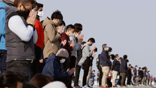 Participants pray and observe a moment of silence towards the sea at 2:46 p.m. (05:46 GMT), the time when the 9.0-magnitude earthquake struck off Japan's coast in 2011, at Arahama district in Sendai, northeastern Japan, March 11, 2021, to mark the 10-year anniversary of the 2011 earthquake and tsunami that killed thousands and set off a nuclear crisis - Sputnik International