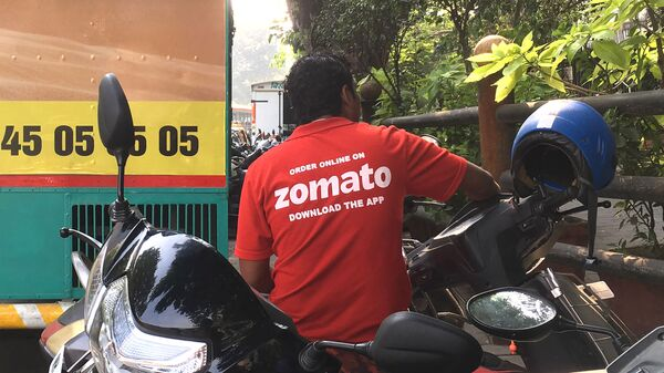 In this photo taken on December 24, 2018, an Indian delivery man working with the food delivery app Zomato sits on his bike in a business district in Mumbai.  - Sputnik International