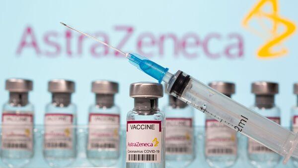 Vials labelled AstraZeneca COVID-19 Coronavirus Vaccine and a syringe are seen in front of a displayed AstraZeneca logo in this illustration taken March 10, 2021. REUTERS/Dado Ruvic/Illustration - Sputnik International