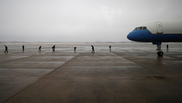 Air Force One crew members scan the tarmac following a previous day ice storm, ahead of U.S. President Joe Biden's trip to Michigan, at Joint Base Andrews in Maryland, U.S., February 19, 2021.  - Sputnik International