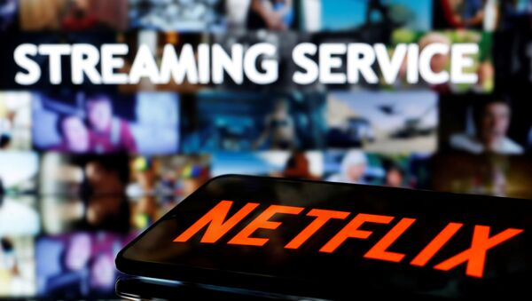 FILE PHOTO: A smartphone with the Netflix logo lies in front of displayed Streaming service words in this illustration taken March 24, 2020 - Sputnik International