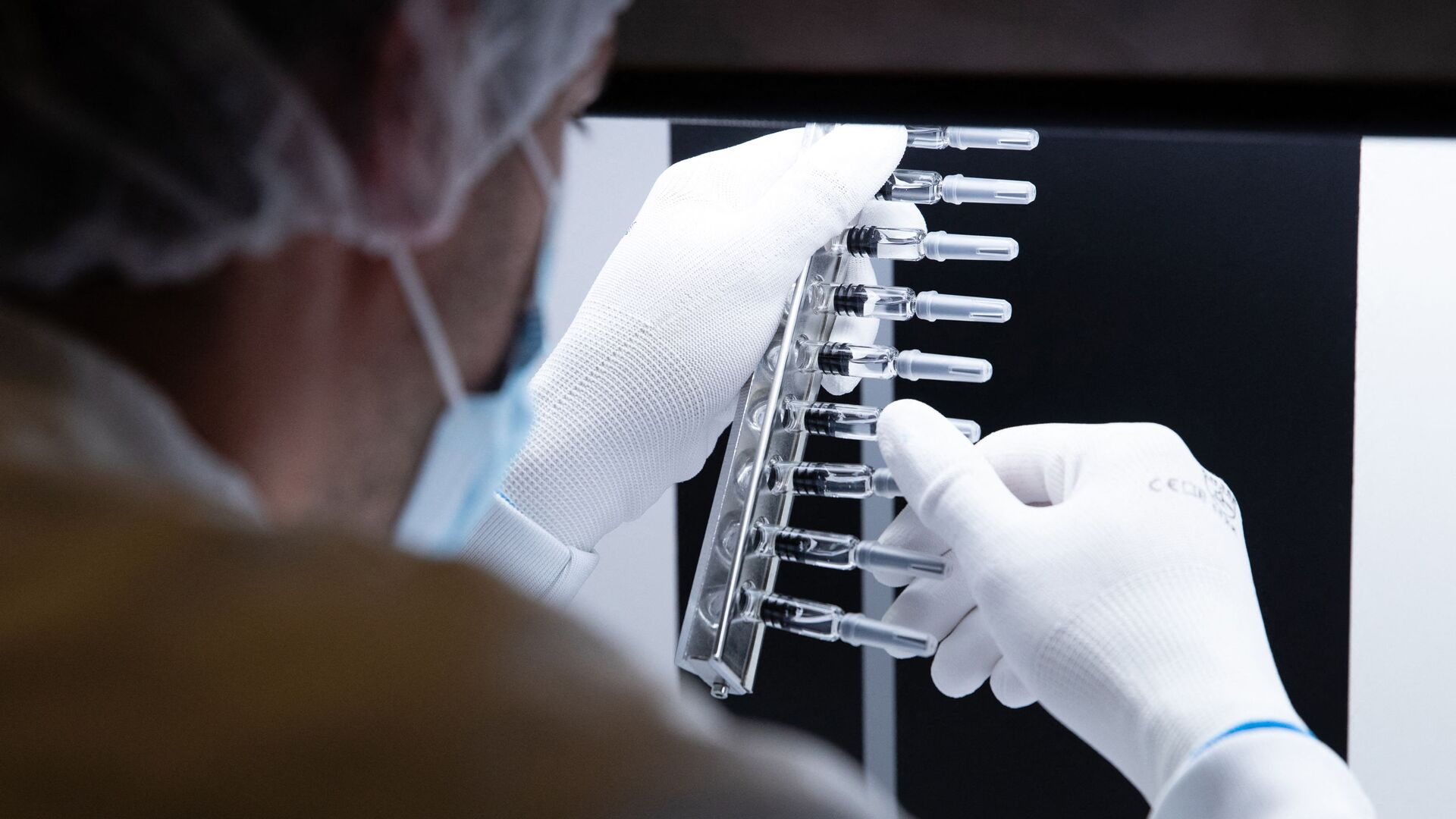 A laboratory technician inspects defunct syringes which were set aside by an automatic inspection machine at a French pharmaceutical company Sanofi's world distribution centre in Val de Reuil on July 10, 2020 - Sputnik International, 1920, 28.09.2021