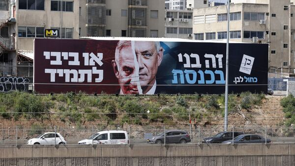 Cars drive past an election campaign billboard for Israel's Blue and White opposition party led by Benny Gantz (R) depicting him and Israeli Prime Minister Benjamin Netanyahu of the Likud party, on a highway in the coastal city of Tel Aviv, on March 12, 2021, ahead of the March 23 general election. The writing in Hebrew reads Benny to the Knesset or Bibi for ever. - Sputnik International