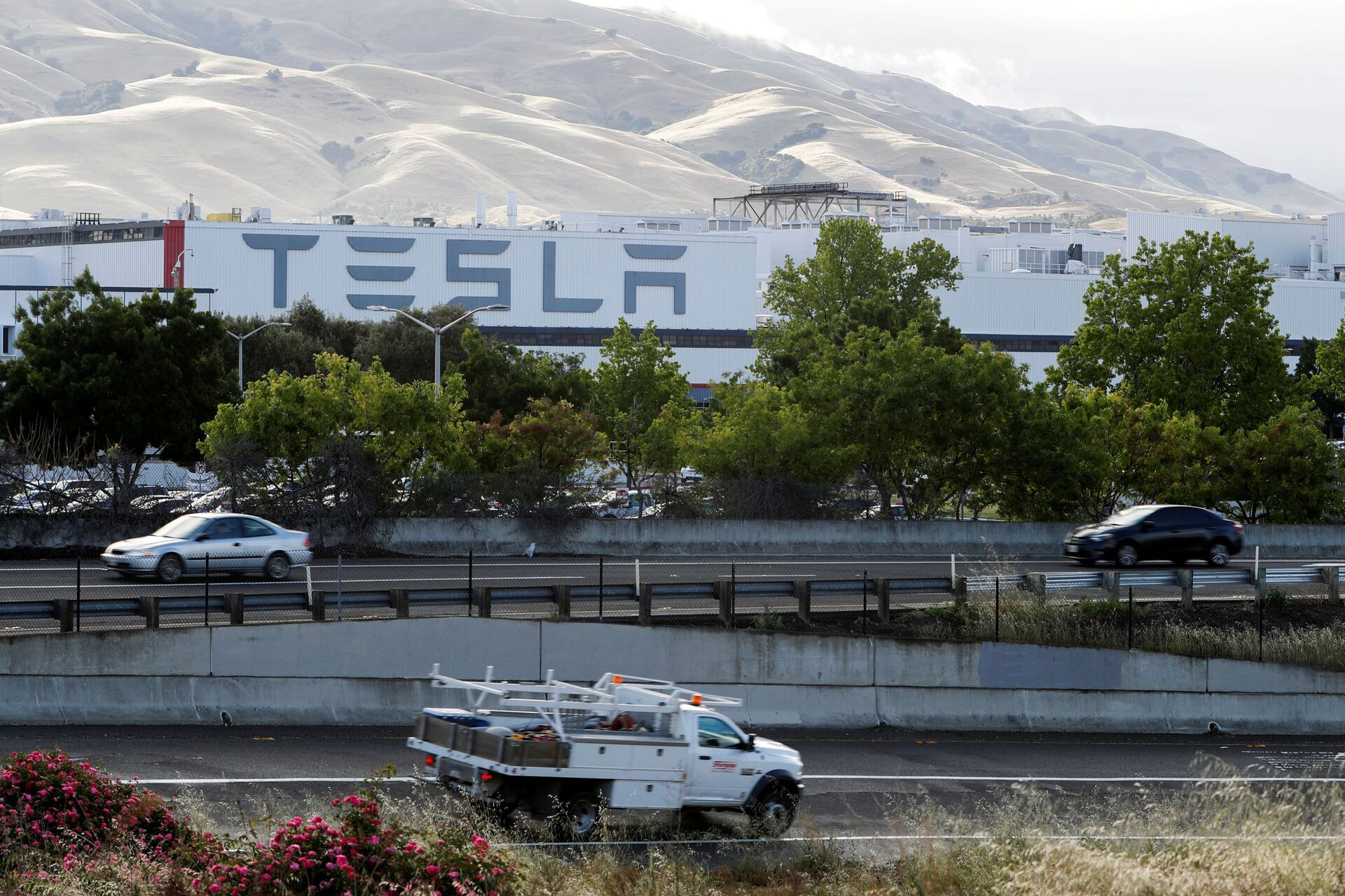 Motorists drive past Tesla's primary vehicle factory after CEO Elon Musk announced he was defying local officials' restrictions against the spread of the coronavirus disease (COVID-19) by reopening the plant in Fremont, California, U.S. May 12, 2020 - Sputnik International, 1920, 07.09.2021