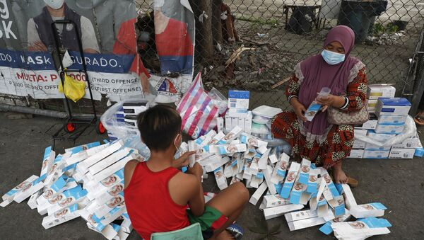 A woman and a boy wearing face masks to prevent the spread of the coronavirus arrange boxes of face shields in Manila, Philippines, Friday, March 12, 2021.  - Sputnik International