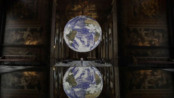 Reflected in a mirrored table Luke Jerram's illuminated 3D installation entitled Gaia, displayed with surround sound from award winning composer Dan Jones, as part of the 2020 Greenwich and Docklands International Festival, at the Royal Naval College in London, 28 August 2020 - Sputnik International