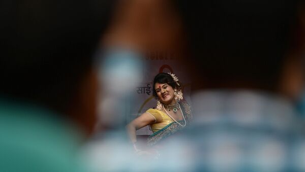 A  traditional Lavani folk dancer is seen through a gap among the audience during a performance for sex workers in the red light district of Kamathipura in Mumbai on 28 August 2015, ahead of the Hindu festival 'Raksha Bandhan' - Sputnik International