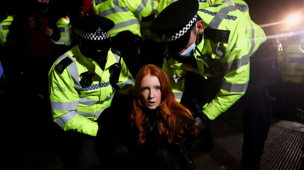 Police detain a woman as people gather at a memorial site in Clapham Common Bandstand, following the kidnap and murder of Sarah Everard, in London, Britain - Sputnik International