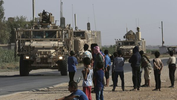 In this July 26, 2017 file photo, Syrian children and youths gather on a street as they look at a U.S. armored vehicle convoy pass on a road that links to Raqqa, northeast Syria. - Sputnik International