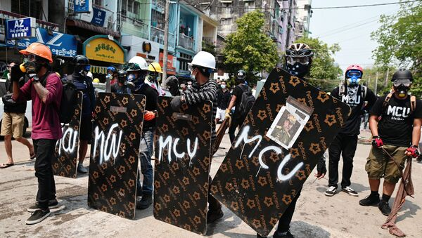 Demonstrators stand behind makeshift shields during an anti-coup protest in Yangon - Sputnik International