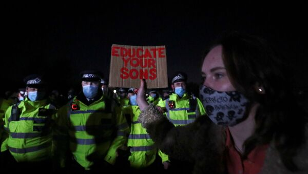 A woman hold a sign in front of police as people gather at a memorial site in Clapham Common Bandstand, following the kidnap and murder of Sarah Everard, in London, Britain March 13, 2021. REUTERS/Hannah McKay - Sputnik International