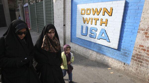 Women walk past  anti-US graffiti painted on the wall of the former US Embassy in Tehran, Iran, Wednesday, Dec. 8, 2010 - Sputnik International