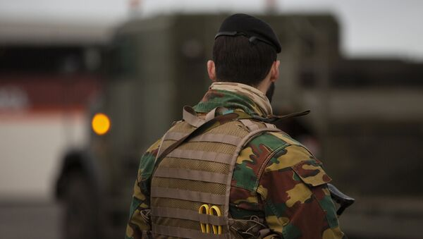 A Belgian solider patrols in a temporary military zone as vehicles arrive from a British naval vessel, taking part in U.S.-led war games, as they are unloaded at the Port of Antwerp in Antwerp, Belgium, Monday Feb. 3, 2020.  - Sputnik International