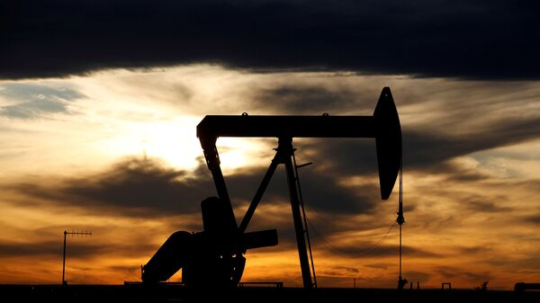 The sun sets behind a crude oil pump jack on a drill pad in the Permian Basin in Loving County, Texas, U.S. November 24, 2019. - Sputnik International