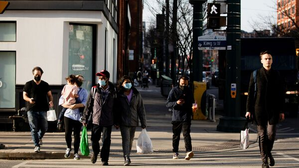 People walk with face masks on the one-year anniversary of the World Health Organization declaring coronavirus disease (COVID-19) a pandemic in Toronto, Ontario, Canada March 11, 2021 - Sputnik International