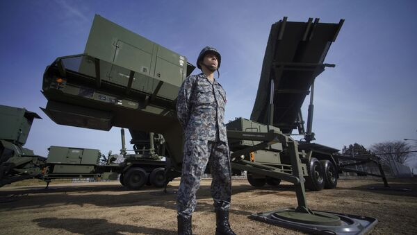 A member of Japan Ground Self-Defense Force stands guard next to a surface-to-air Patriot Advanced Capability-3 (PAC-3) missile interceptor launcher vehicle - Sputnik International