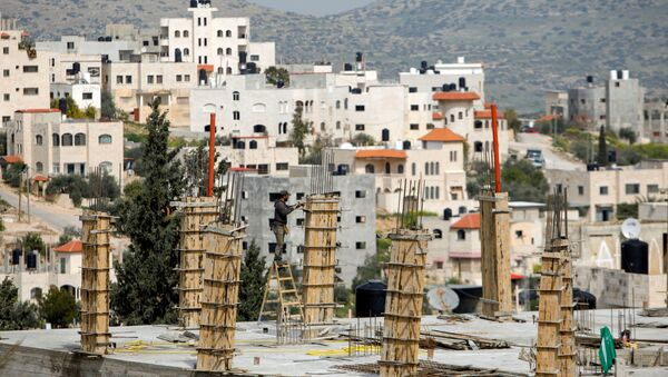 A Palestinian laborer works at the construction site of a house during a lockdown imposed to prevent the spread of the coronavirus disease (COVID-19), in Tubas in the Israeli-occupied West Bank March 15, 2021 - Sputnik International
