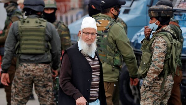 A Kashmiri Muslim man walks past Indian security force personnel standing guard during a cordon and search operation, in Srinagar February 26, 2021 - Sputnik International