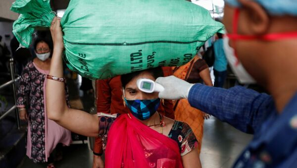 A health worker checks the temperature of a passenger, amid the spread of the coronavirus disease (COVID-19), at a railway station in Mumbai, India, March 17, 2021 - Sputnik International