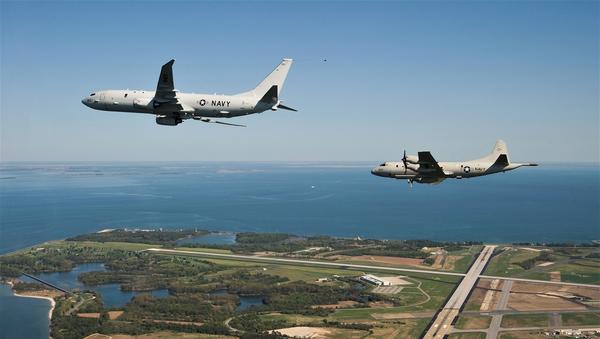 The first P-8A Poseidon test aircraft, followed by its propeller-driven P-3C predecessor, flies past NAS Patuxent River. File photo. - Sputnik International