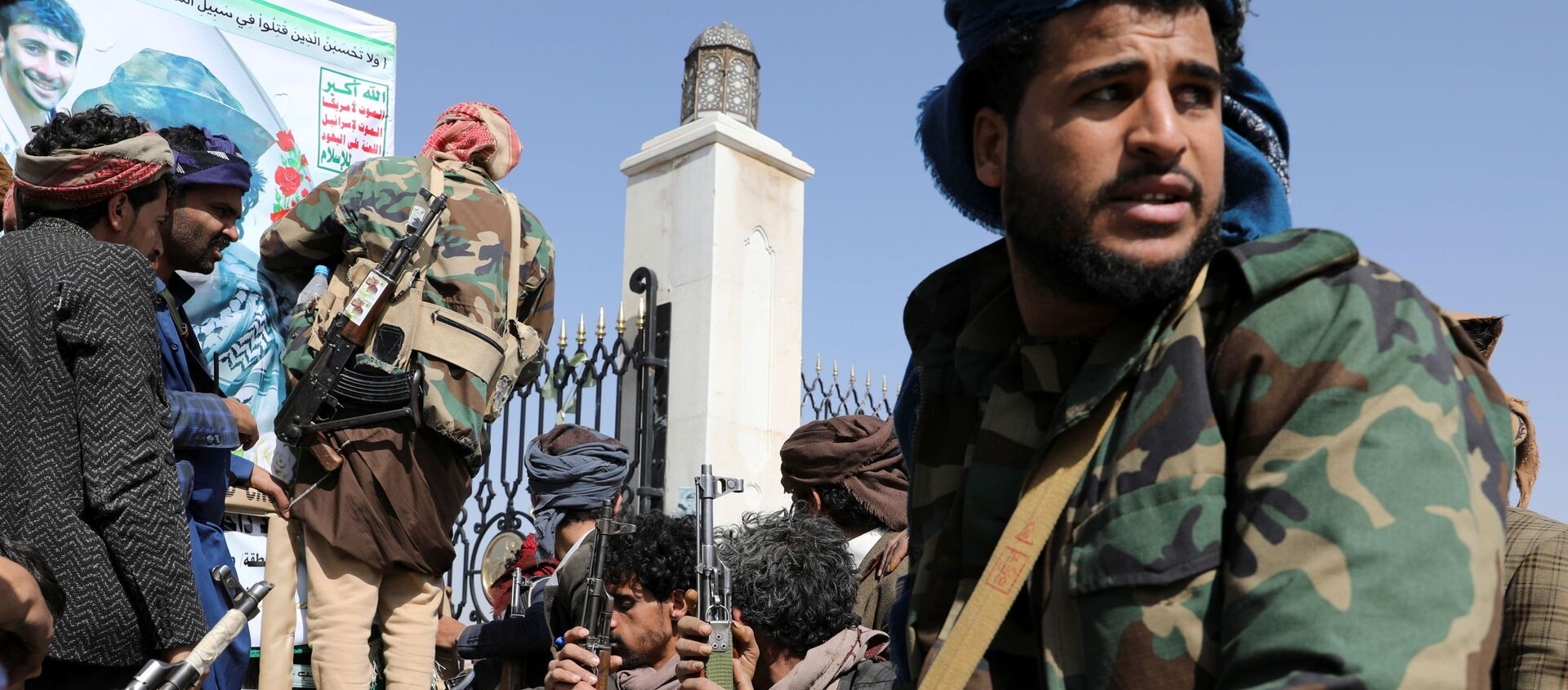 Armed Houthi followers sit next to a coffin of a Houthi fighter killed in recent fighting against government forces in Yemen's oil-rich province of Marib, during a funeral procession in Sanaa, Yemen February 20, 2021. - Sputnik International, 1920, 20.05.2021