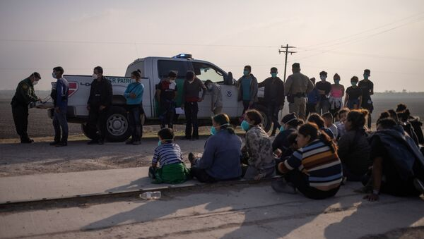 A U.S. Border Patrol agent processes asylum-seeking unaccompanied minors as family units sit on the sideline after about 70 migrants crossed the Rio Grande river into the United States from Mexico on a raft in Penitas, Texas, U.S., March 17, 2021. - Sputnik International