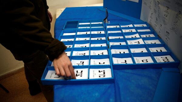 An Israeli soldier sorts ballot papers at a mobile voting booth set-up for soldiers to cast their early vote in the March 23 general election, amid the coronavirus disease (COVID-19) crisis, at a military base, near Kibbutz Regavim, Israel March 17, 2021. - Sputnik International