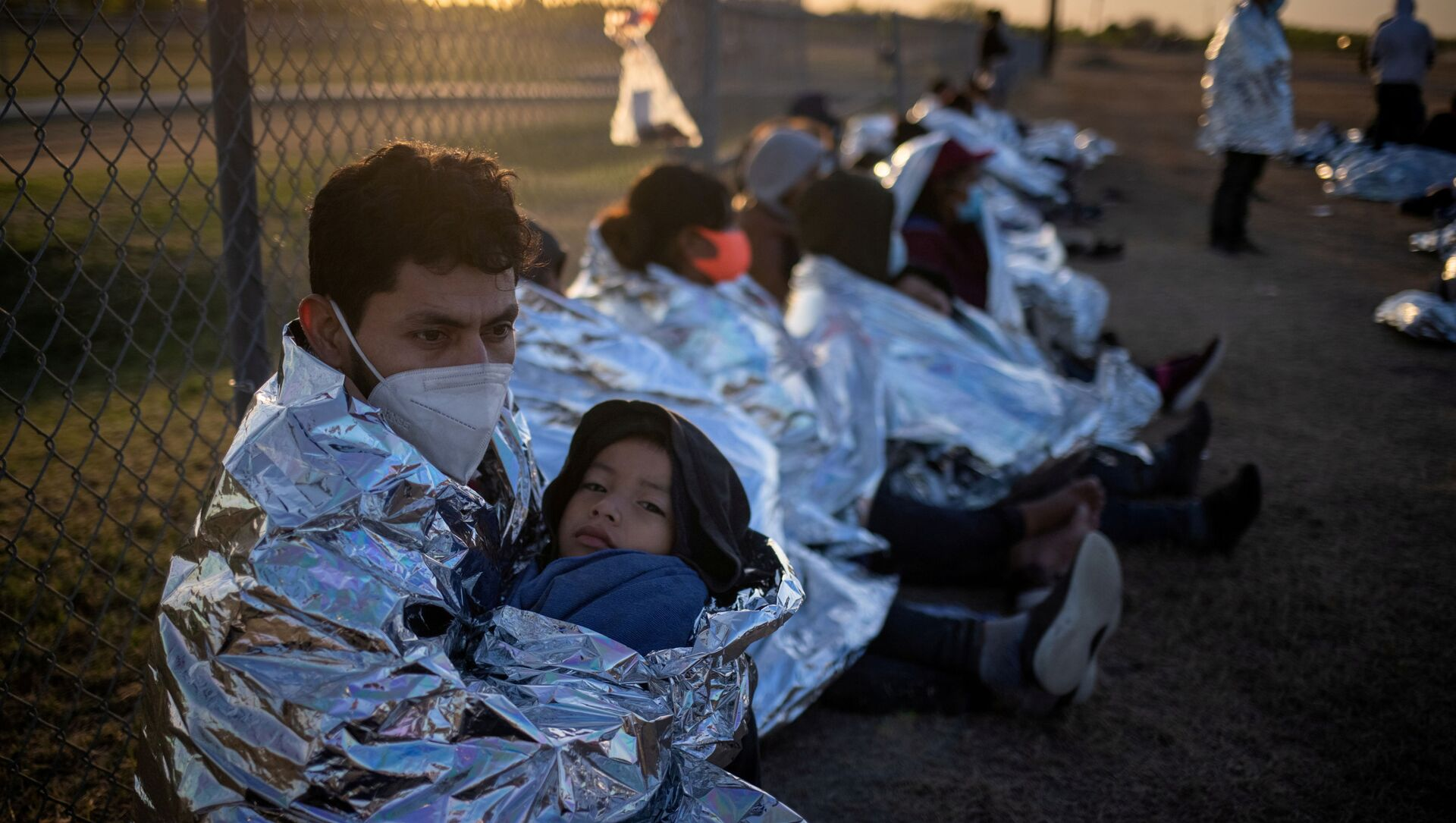 Dustin, an asylum-seeking migrant from Honduras, holds his six-year-old son Jerrardo, 6, as they awake at sunrise next to others who took refuge near a baseball field after crossing the Rio Grande river into the United States from Mexico on rafts, in La Joya, Texas, U.S., March 19, 2021. Emergency blankets were provided to the group of about 150 migrants from Central America by the U.S. Border Patrol agents.  - Sputnik International, 1920, 09.05.2021