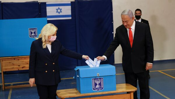 Israeli Prime Minister Benjamin Netanyahu and his wife Sara cast their ballots at a polling station as Israelis vote in a general election, in Jerusalem March 23, 2021 - Sputnik International