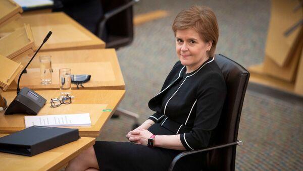 Scotland's First Minister Nicola Sturgeon sits at the main chamber ahead of a coronavirus disease (COVID-19) briefing at the Scottish Parliament in Holyrood, Edinburgh, Scotland, Britain March 23, 2021. - Sputnik International