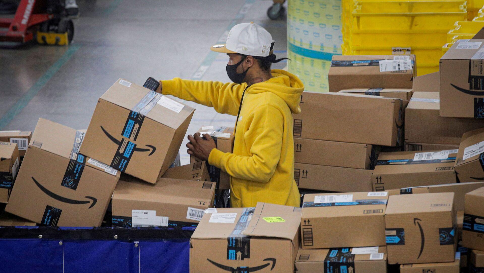 FILE PHOTO: An employee scans packages at Amazon's JFK8 distribution center in Staten Island, New York, U.S. November 25, 2020.  - Sputnik International, 1920, 03.08.2021