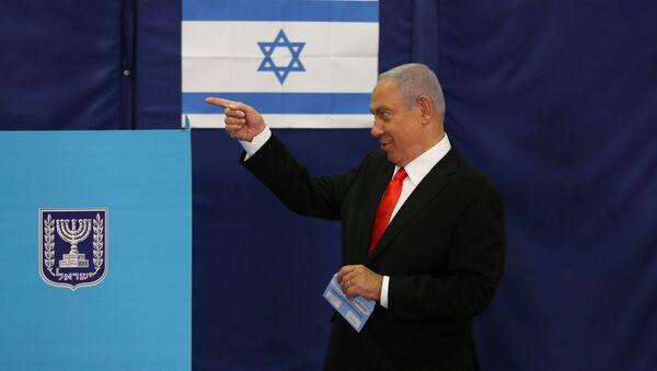 Israeli Prime Minister Benjamin Netanyahu gestures while standing near a voting booth as he prepares to cast his ballot in Israel's general election, at a polling station in Jerusalem March 23, 2021 - Sputnik International