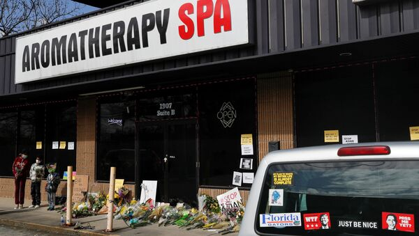 Children holding flowers stand during a vigil at a makeshift memorial outside the Aromatherapy Spa following the deadly shootings in Atlanta, Georgia, U.S. March 21, 2021 - Sputnik International