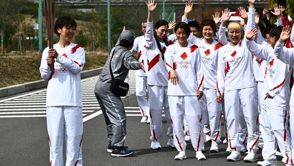 Japanese torchbearer Azusa Iwashimizu (L), a member of the Japan women's national football team, holds an Olympic Torch after passing the flame to the next torchbearer during the torch relay grand start at the J-Village National Training Centre in Naraha town, Fukushima Prefecture, Japan March 25, 2021.  - Sputnik International