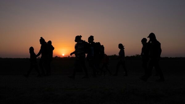 The sun rises as asylum-seeking migrants' families from Honduras and El Salvador walk towards the border wall after crossing the Rio Grande river into the United States from Mexico on a raft, in Penitas, Texas, 26 March 2021 - Sputnik International