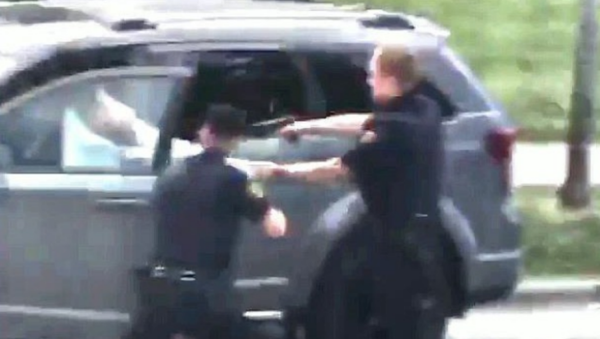 A still from cell phone footage included in the federal complaint against Kenosha Police Officer Rusten Sheskey by Jacob Blake, a 29-year-old Black man who Sheskey shot six times in the back during an August 23, 2020 encounter. In the image, Sheskey is holding onto the back of Blake's shirt as he fires into Blake's back. - Sputnik International