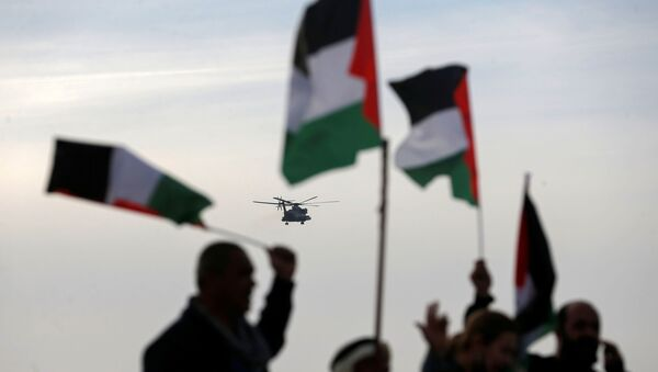 Demonstrators hold Palestinian flags as an aircraft carrying Israeli Prime Minister Benjamin approaches to land near the heritage site of ancient Susya, during a protest against Netanyahu's visit to the site, in Susya village in the Israeli-occupied West Bank March 14, 2021.  - Sputnik International